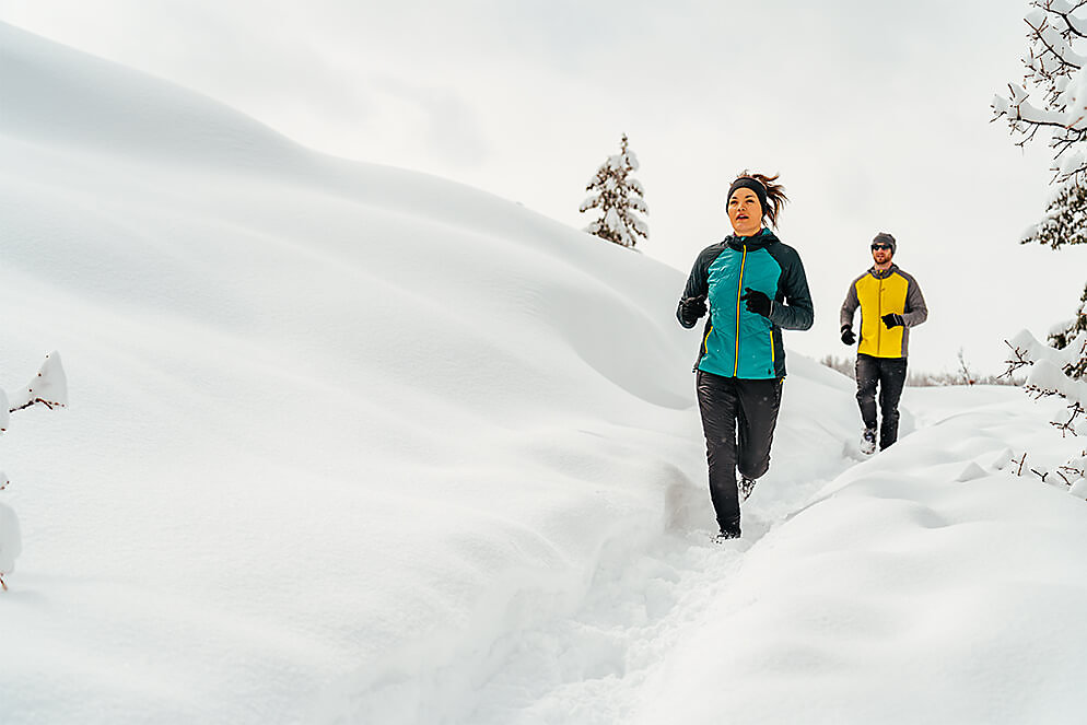 Man and woman running along snowy bridge