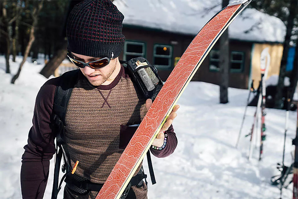Man in beanie and sunglasses carrying skis