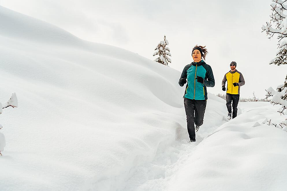 Man and woman running along snowy bridge