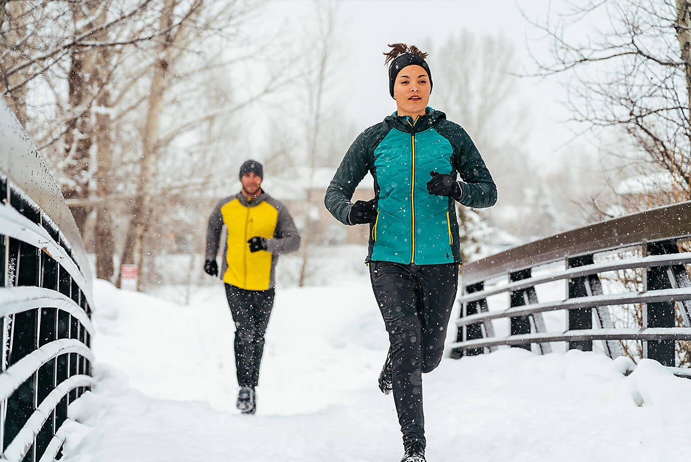 Man and woman running along snowy trail
