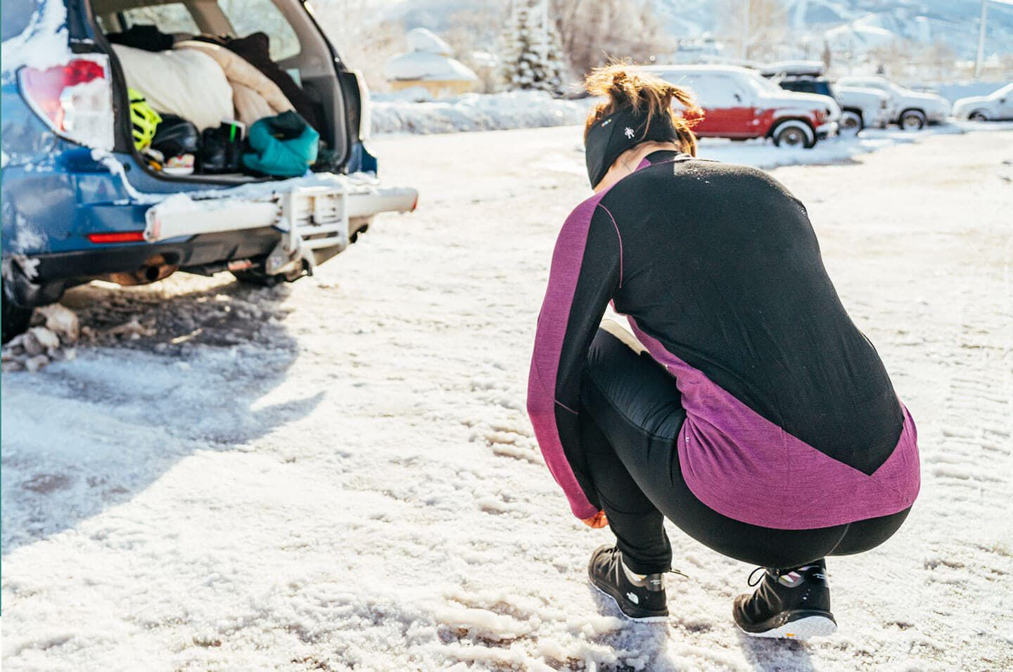 Woman tying shoes behind parked car