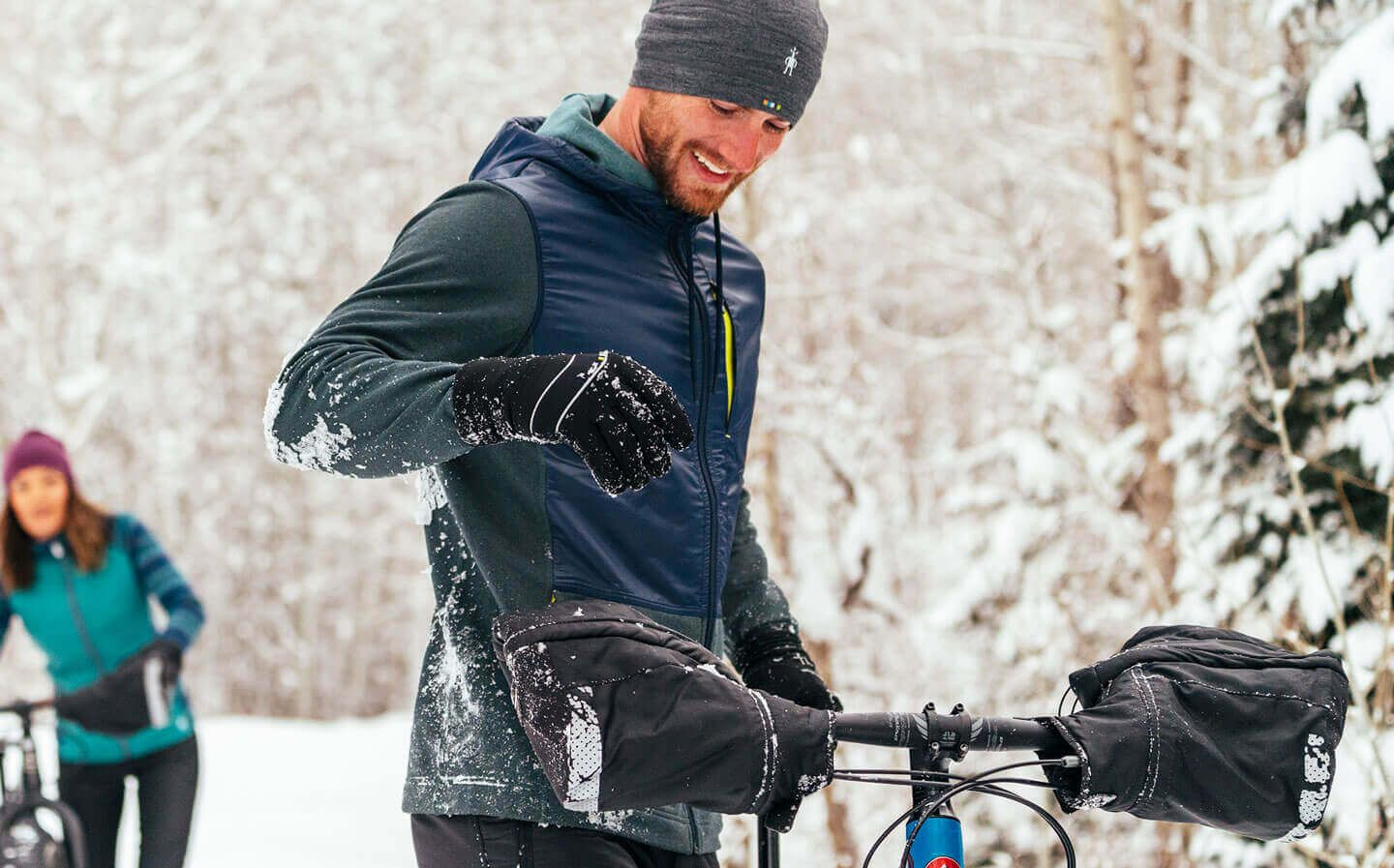 Man and woman walking with fat bikes in snow