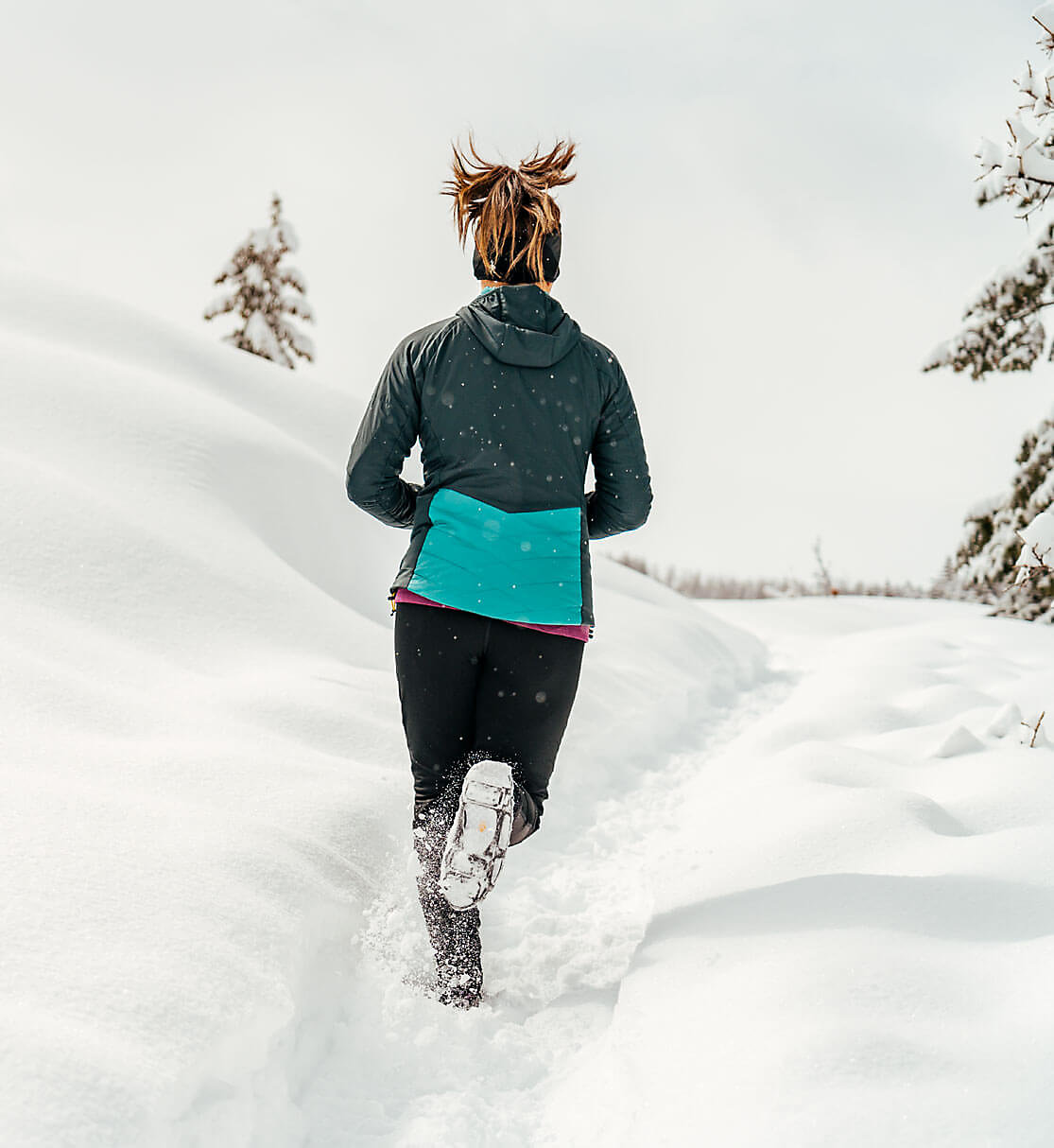Shot from behind of woman running up snowy trail